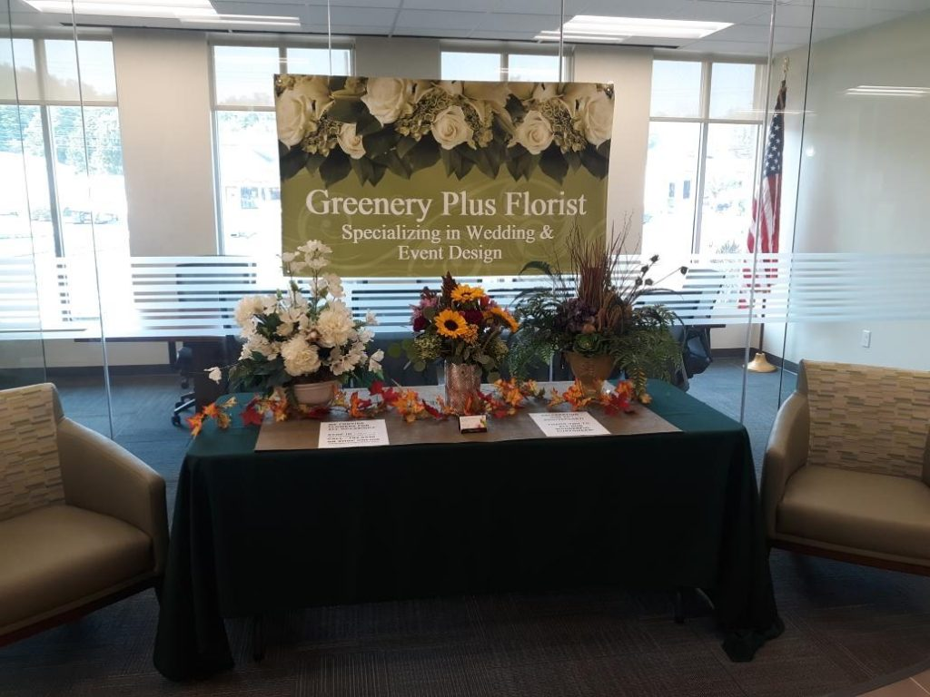 Business display table for Greenery Plus Florist decorated with flowers and signs.