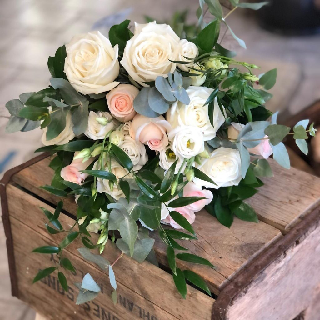 White and blush rose bouquet on wooden box
