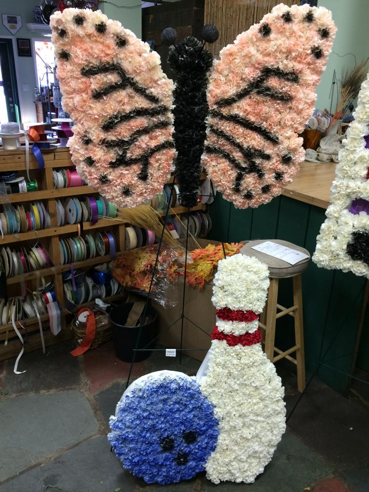 flower arrangements made to look like a butterfly and bowling ball and pin